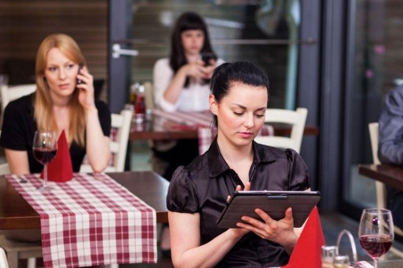 Woman using a tablet computer in a restaurant