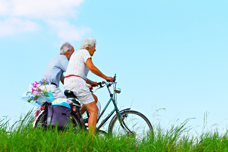Two elderly individuals cycling